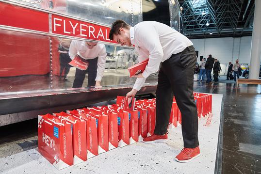 Mitarbeiter verteilen auf einer B2B-Messe Goodie-Bags